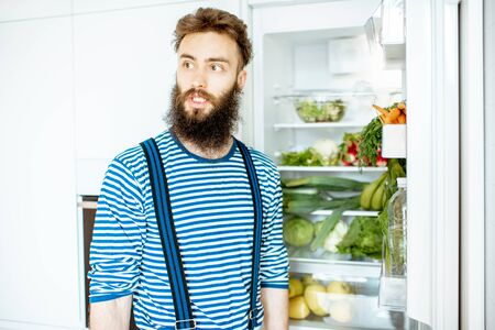 Portrait of a well-looking man standing near the fridge full of fresh vegetables and fruits at home