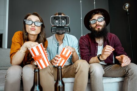 Friends watching movie with 3d goggles while sitting together with pop corns on the couch at home