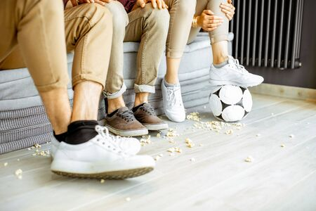 Friends watching football match. View on their legs with pop cornes and ball on the floor Stockfoto