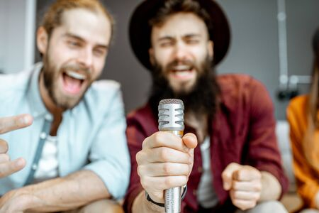 Two male friends singing hard with microphone while playing karaoke at home