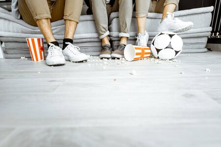 Friends watching football match. View on their legs with pop cornes and ball on the floor. Image with copy space