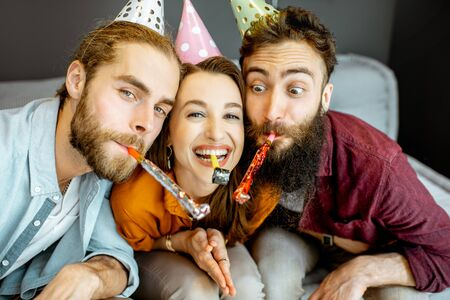 Young friends having fun with whistles during the party or birthday celebration at home