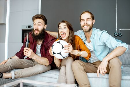 Young friends watching football match, cheering up for a favorite team while sitting together with drinks and ball on the couch at home Stockfoto