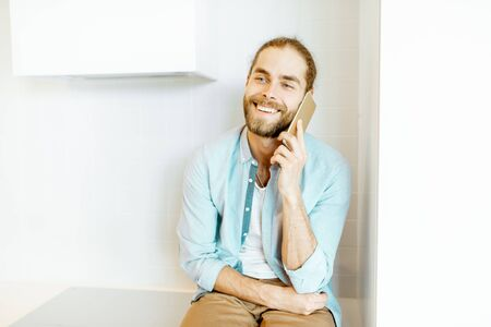 Portrait of a handsome man talking with phone while sitting on the white kitchen at home