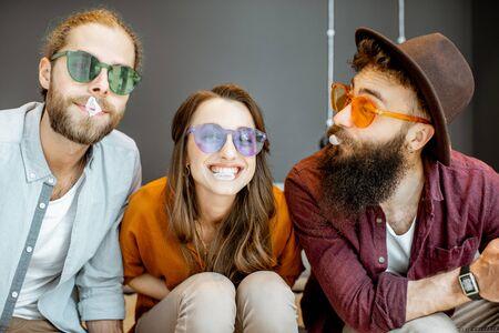 Junge Freunde in bunten Gläsern haben Spaß mit Kaugummiblasen, die zu Hause zusammensitzen Standard-Bild