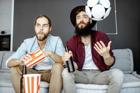 Two male friends watching football match, cheering up for the sports team while sitting with drinks and pop cornes on the couch at home Stockfoto