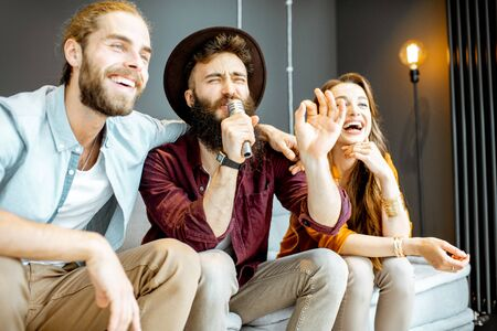 Young and cheerful friends singing with microphone while playing karaoke at home Stockfoto