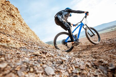 Professional well-equiped cyclist riding down on the rocky mountains. Concept of a freeride and off road cycling 写真素材