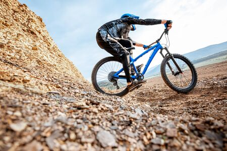 Professional well-equiped cyclist riding down on the rocky mountains. Concept of a freeride and off road cycling