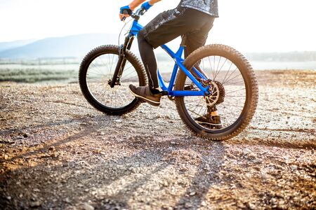 Man riding bicycle on the rocky mountains, cropped image with no face