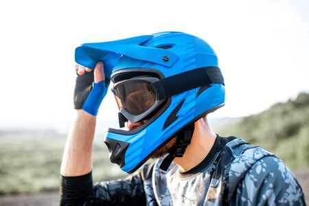 Portrait of a well-equipped rider wearing full-face helmet outdoors Stock Photo