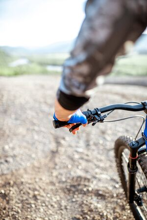 Man riding bicycle on the rocky mountains, close-up view on the hands and helm 写真素材