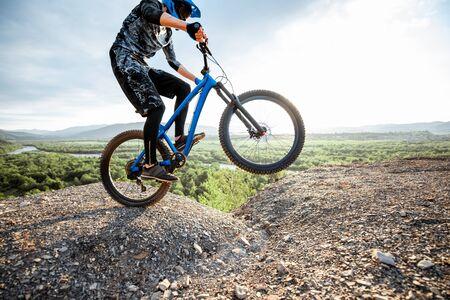 Ciclista profesional bien equipado montando bicicleta en las montañas rocosas con hermosas vistas al paisaje durante la puesta de sol
