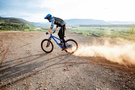 Ciclista profesional bien equipado que monta extremadamente en las montañas rocosas levantando polvo durante la puesta de sol