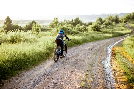 Professional well-equipped cyclist riding down on the mountain road during the sunset