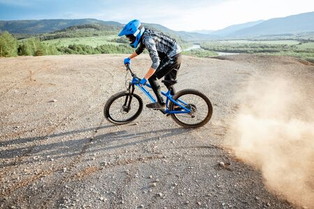 Professional well-equipped cyclist riding extremely on the rocky mountains raising dust behind during the sunset
