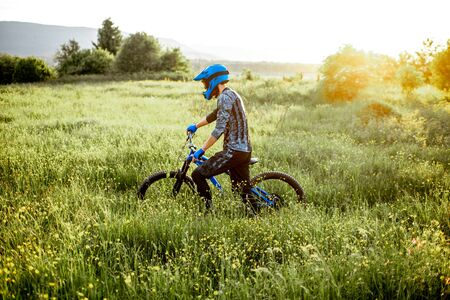 Professional well-equipped cyclist walking with bicycle on the beautiful green field on the mountains during the sunset Foto de archivo - 125076246