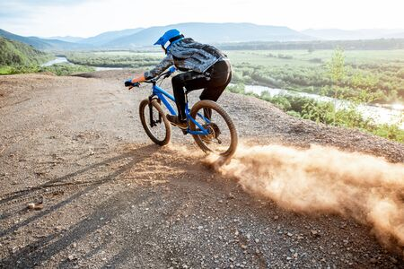 Professional well-equipped cyclist riding extremely on the rocky mountains raising dust behind during the sunset Foto de archivo - 125076247