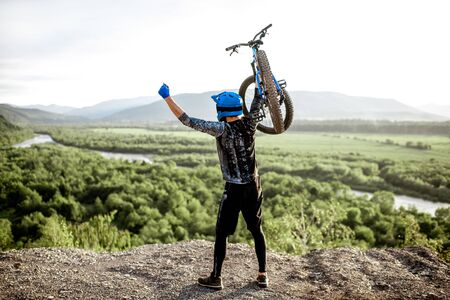 Professional well-equipped cyclist raising hands with bicycle while standing on the top of the mountain Foto de archivo - 125076250