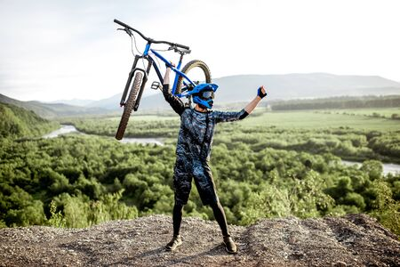 Professional well-equipped cyclist raising hands with bicycle while standing on the top of the mountain Stock Photo