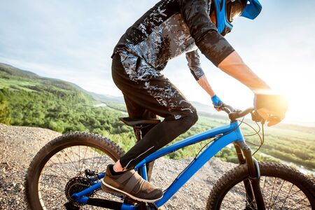 Professional well-equipped cyclist riding bicycle on the rocky mountains with beautiful landscape view during the sunset Foto de archivo - 125076249