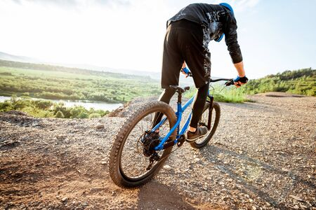 Professional well-equipped cyclist riding bicycle on the rocky mountains with beautiful landscape view during the sunset Foto de archivo - 125076252