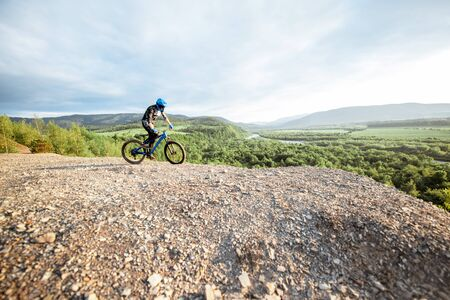 Professional well-equipped cyclist riding bicycle on the rocky mountains with beautiful landscape view during the sunset. wide view with copy space