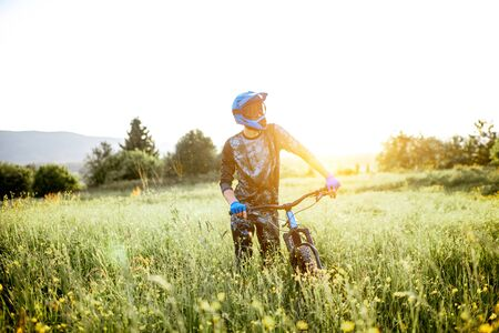 Portrait of a professional well-equipped cyclist walking with bicycle on the beautiful green field on the mountains during the sunset