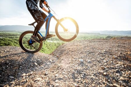 Professional well-equipped cyclist riding bicycle on the rocky mountains with beautiful landscape view during the sunset 写真素材