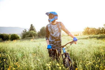 Portrait of a professional well-equipped cyclist walking with bicycle on the beautiful green field on the mountains during the sunset Foto de archivo - 125076261