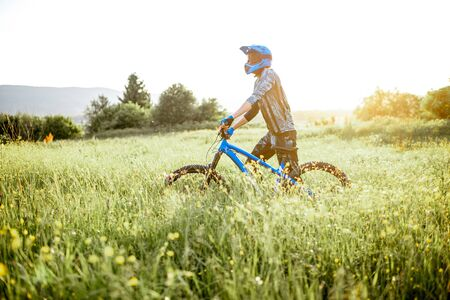 Professional well-equipped cyclist walking with bicycle on the beautiful green field on the mountains during the sunset Foto de archivo - 125076263