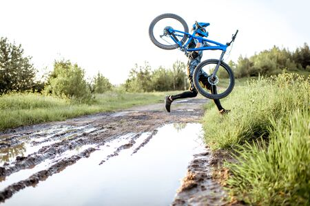Professional well-equipped cyclist jumping through the puddle on the mountain dirt road during the sunset