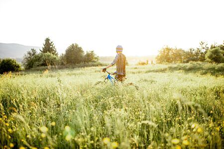 Professional well-equipped cyclist walking with bicycle on the beautiful green field on the mountains during the sunset