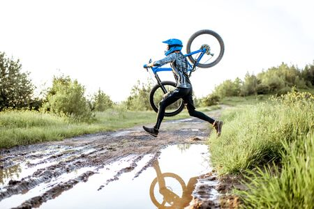 Professional well-equipped cyclist jumping through the puddle on the mountain dirt road during the sunset Foto de archivo - 125076360