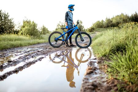 Professional well-equipped cyclist crossing mountain dirt road with puddles during the sunset 写真素材