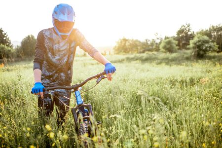 Portrait of a professional well-equipped cyclist walking with bicycle on the beautiful green field on the mountains during the sunset Foto de archivo - 125076365