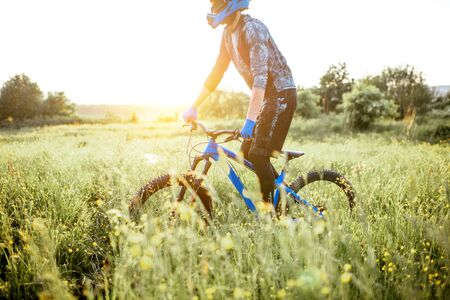 Professional well-equipped cyclist riding on the beautiful green field on the mountains during the sunset