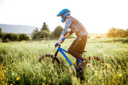 Professional well-equipped cyclist riding on the beautiful green field on the mountains during the sunset Foto de archivo - 125076366