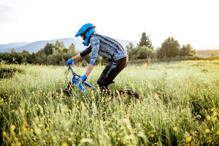 Professional well-equipped cyclist riding on the beautiful green field on the mountains during the sunset Foto de archivo - 125076367