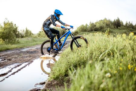 Professional well-equipped cyclist crossing mountain dirt road with puddles during the sunset Foto de archivo - 125076369