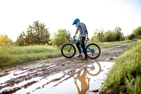 Professional well-equipped cyclist crossing mountain dirt road with puddles during the sunset Foto de archivo - 125076370