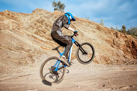 Professional well-equipped cyclist riding bicycle on the rocky mountains. Concept of a freeride and off road cycling
