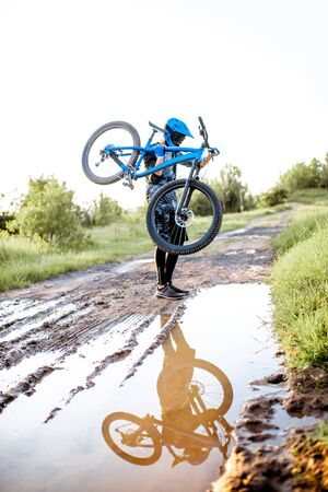Professional well-equipped cyclist crossing mountain dirt road with puddles during the sunset Foto de archivo - 125076378