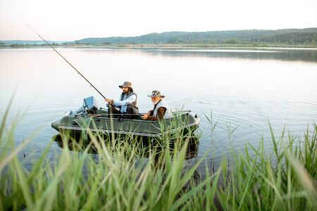 Grandfather with adult son fishing on the inflatable boat on the lake with green cane on the foreground early in the morning