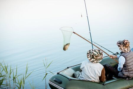 Grandfather with adult son fishing on the inflatable boat, catching fish with net on the lake early in the morning