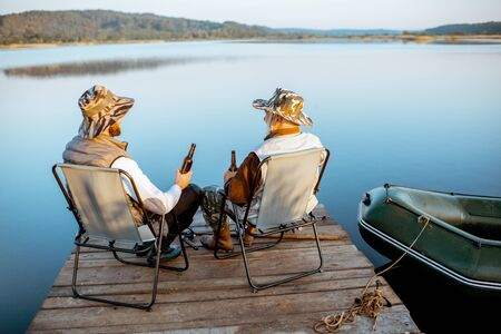 Grandfather with adult son enjoying beer, sitting together on the pier while fishing on the lake early in the morning Фото со стока