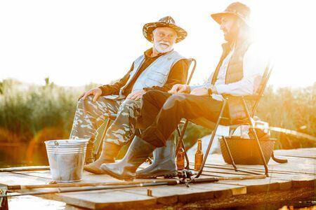 아침 햇살 동안 나무 부두에서 함께 낚시를 하는 성인 아들과 함께 할아버지. 호수 쪽에서 본 모습 스톡 콘텐츠