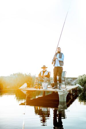 Grandfather with adult son fishing together on the wooden pier during the morning light. View from the side of the lake