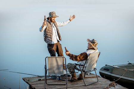 Grandfather with adult son having warm conversation while fishing together on the pier near the lake early in the morning Banque d'images