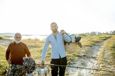 Gandfather with adult son walking for fishing during the morning light near the lake